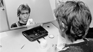 A photograph of Peter Gabriel looking at himself in the mirror taken in the 80s