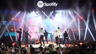 South Korean boy band Stray Kids perform on stage underneath a Spotify banner