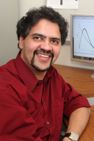 Yogesh Joglekar sits at a desk wearing a red button down shirt.