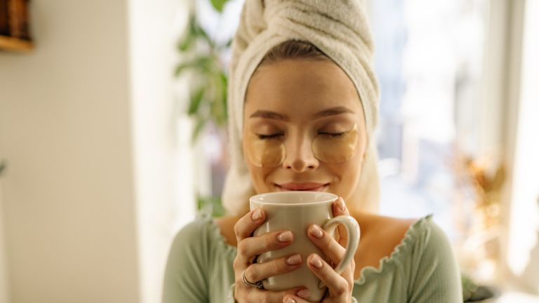 Woman wearing towel around her head and enjoying a hot drink