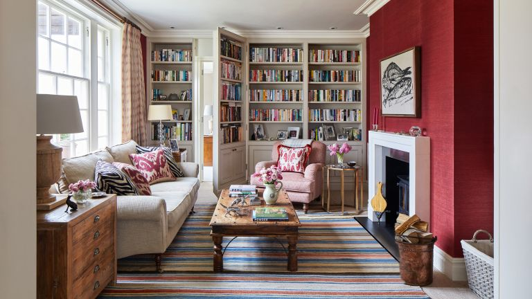 Crimson painted living room with large book case and sofa