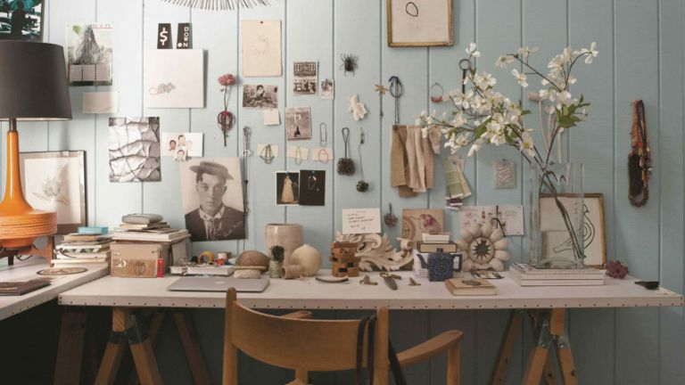desk with blue panelled wall and lots of decor pieces