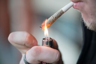 Man smoking marijuana cigarette soft drug in Amsterdam, Netherlands.