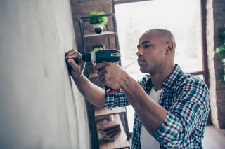 man using drill on wall