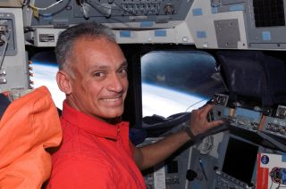 NASA astronaut Danny Olivas smiles on the flight deck of space shuttle Atlantis during the STS-117 mission to the International Space Station in June 2007