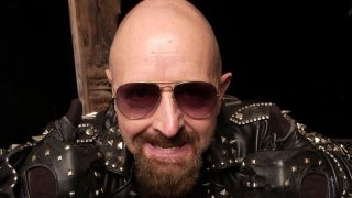 Judas Priest singer Rob Halford wearing sunglasses and leather and leering into the camera