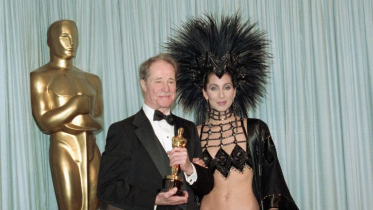 Don Ameche holding the Best Supporting Actor Oscar award for his role in Cocoon, backstage at the Academy Awards with award presenter Cher, who is wearing an unusual Bob Mackie evening gown with a feather headdress.