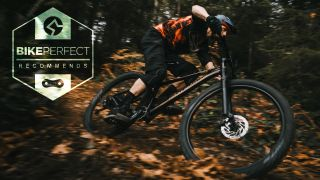 A rider corners around a berm on one of the best hardtail mountain bikes under $1,500