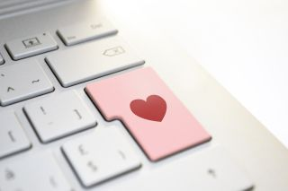 Computer keyboard with heart on large key.