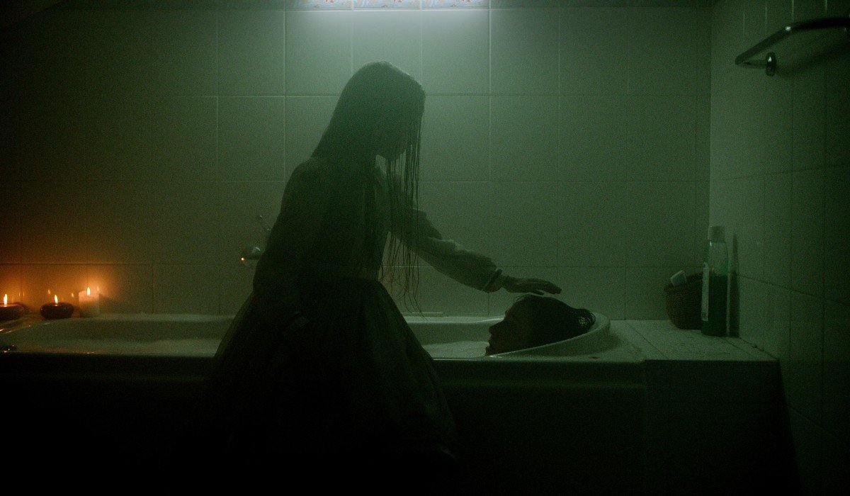 Haunted girl patting head of woman in tub Netflix