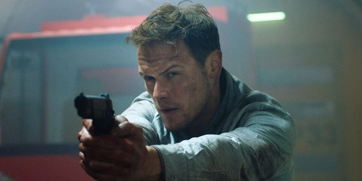 Sam Heughan dirtied up, and aiming a gun in a tunnel, in SAS: Red Notice.