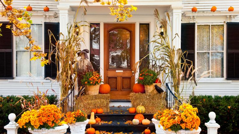 halloween porch decor with pumpkins and corn