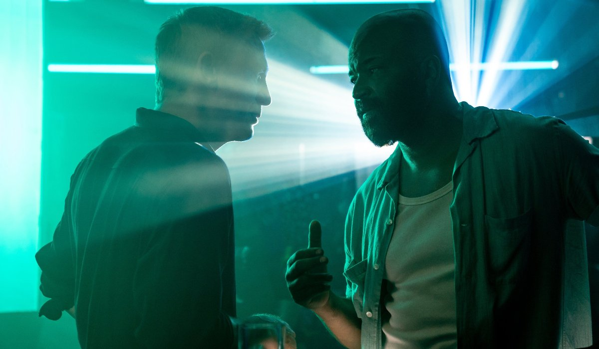 No Time To Die Daniel Craig and Jeffrey Wright talking in a bright, colorful bar