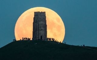 On Sept. 27, 2015, the supermoon rises behind Glastonbury Tor in Glastonbury, England.