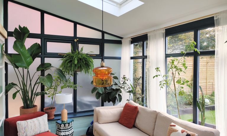 Blue painted conservatory with black painted uPVC window frames and 70s glass ceiling pendant lighting