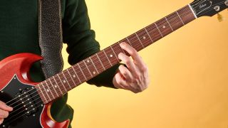 Close-up of guitarist playing a minor chord on a Gibson SG