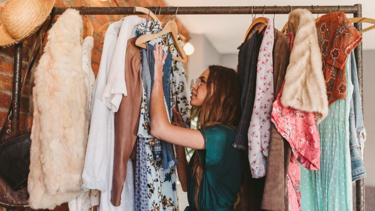 best dresses – woman hangs clothes on rack at home
