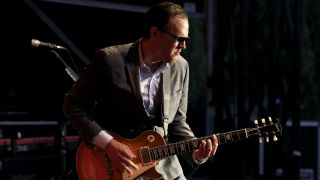 Joe Bonamassa, wearing a suit, playing live on stage