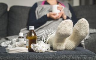 A person sick with a cold sitting on couch.