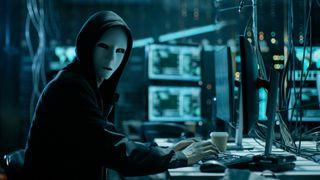 Hacker wearing white mask stares at camera