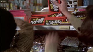 Children's hands grabbing Wonka bars from a shelf