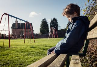 A worried little boy sitting on a bench at a playground.