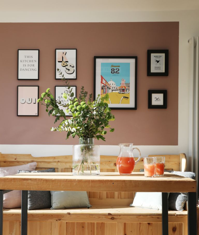 Pink wall with gallery wall of art prints in a dining area