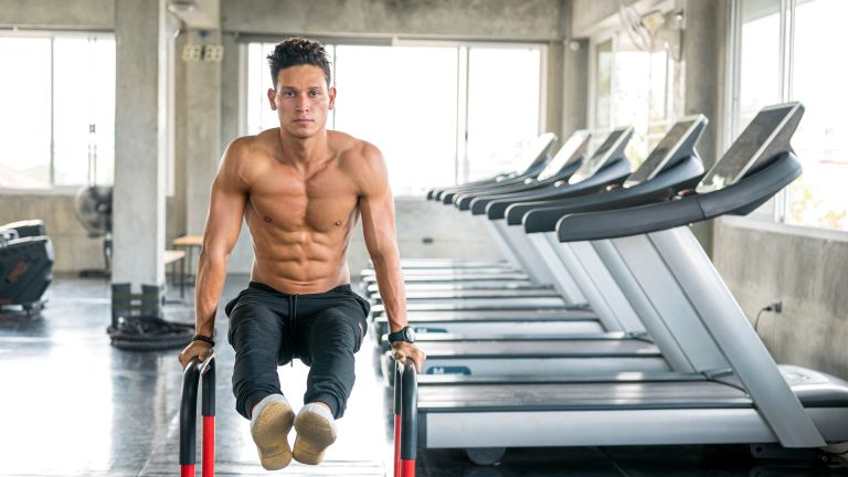 How to get abs: a man with a toned torso works out in a gym