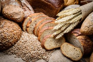 An image of a bunch of whole grains including bread and wheat stalks.