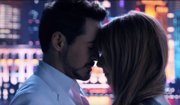 Iron Man 3 Tony and Pepper getting close in front of a cityscape