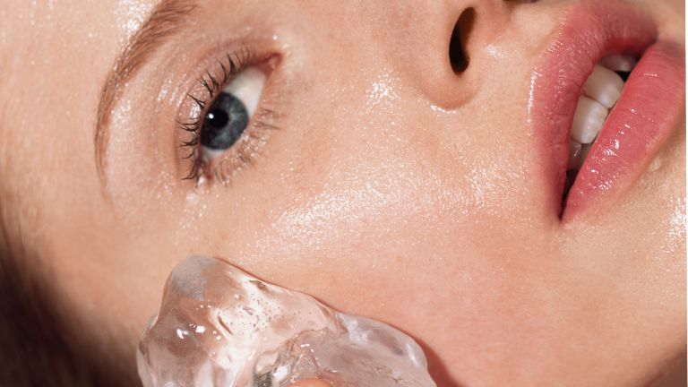 Woman putting ice on her face - stock photo