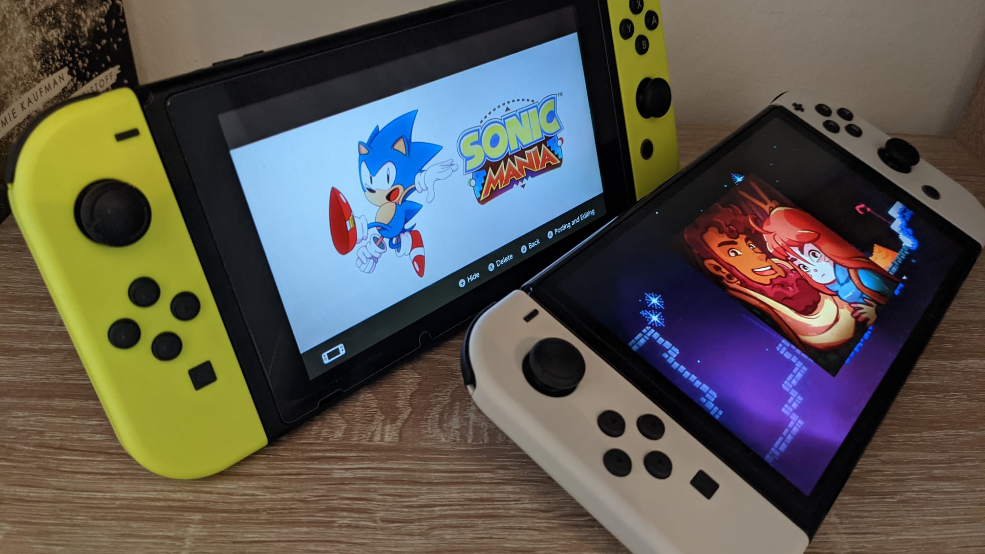 Nintendo Switch OLED showing Celeste and old Switch showing Sonic Mania