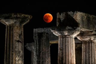 The longest blood moon eclipse of the century occurred on July 27, 2018. Here, the lunar eclipse on that night can be seen over the temple of Apollo in Corinth in Greece.