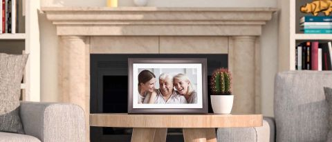 Dragon Touch Classic 10 Digital Picture Frame displaying a family while sitting on a living room table