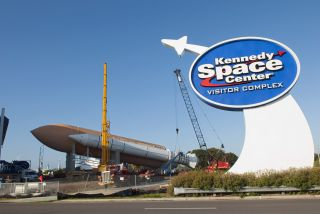 Cranes remove a full-size, 149-foot-long, space shuttle solid rocket booster, or SRB, from NASA's Kennedy Space Center Visitor Complex in Florida to make way for a new exhibit featuring space shuttle Atlantis, which is currently undergoing preparations to