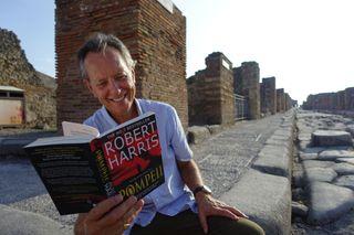 Richard E Grant reading 'Pompeii' in Pompeii.