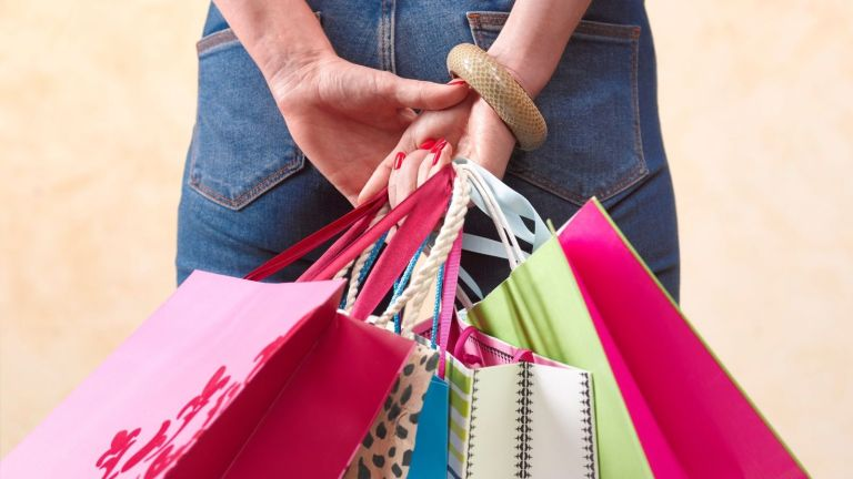 Memorial Day sales: woman holding multi-colored shopping bags from various stores