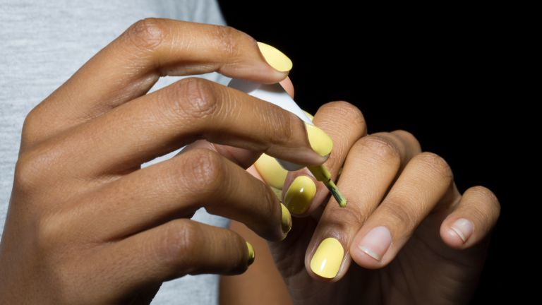 Close-up of woman applying nail varnish, with black background