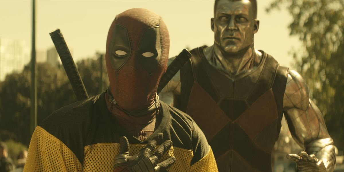 Deadpool with his hand on his heart, standing in front of Colossus, in Deadpool 2.