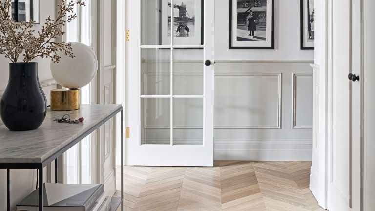 Small hallway ideas with wood floor and white walls with black and white photographs on them.