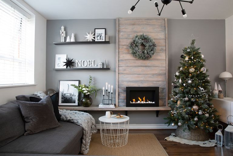 Grey sofa with wooden panelled fireplace, Christmas tree, brown weave rug and black shelving with 'Noel' letter decorations and a pine cone wreath