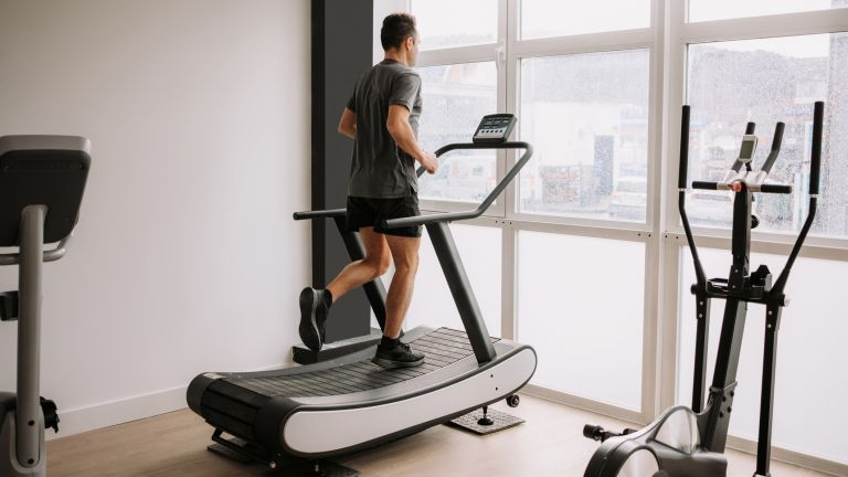 Person running on one of the best treadmills, the Assault Airrunner, looking out of a window