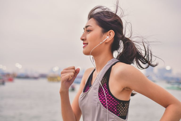 Woman Listening Music While Jogging By River Against Sky - two workouts a day