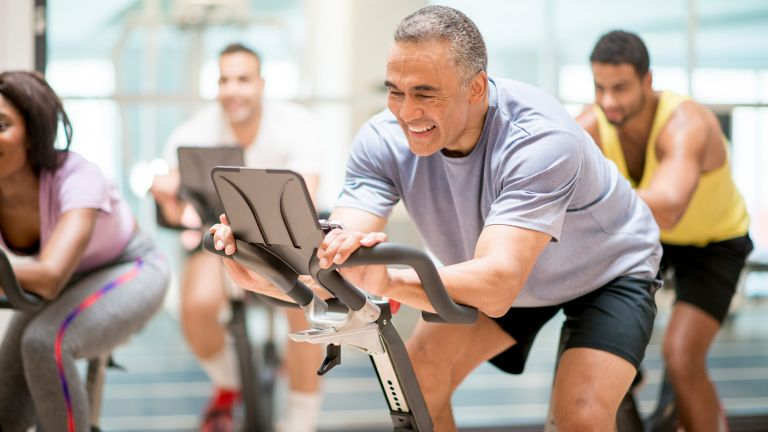 Men and women in a spin class exercising over 50