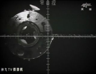 A giant screen at the Jiuquan space center shows the Tiangong-1 space lab from a camera in the Shenzhou-9 spacecraft before the automatic docking on July 18, 2012. The Chinese space lab is expected to re-enter our atmosphere between March 30 and April 2,