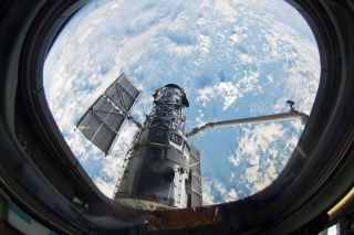 A view of the Hubble Space Telescope through the window of the space shuttle Atlantis, which brought astronauts on a repair mission in 2009.