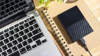 Compact black hard drive sits alongside a MacBook Pro laptop