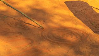 Aboriginal people creating shapes with red sand on the ground in Aboriginal art style.