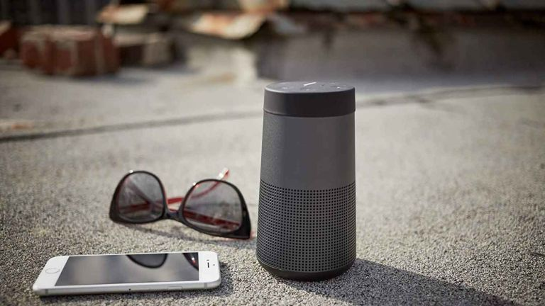 Bose SoundLink Revolve Bluetooth speaker outside on floor with sunglasses and phone