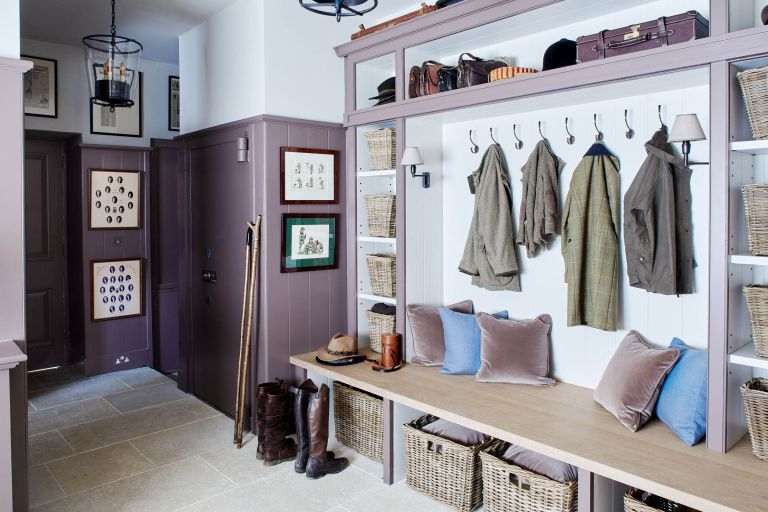 A large mudroom with purple wall paneling and a wooden bench with velvet cushions